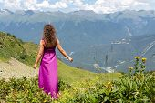 stock photo of mountain chain  - woman in evening dress standing back in the mountains - JPG