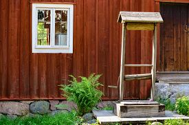 stock photo of fern  - An old weathered water well with a crank outside a red wooden house - JPG