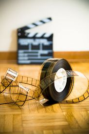 foto of mm  - 35 mm cinema film reel and out of focus movie clapper board in background on wooden floor vertical frame - JPG