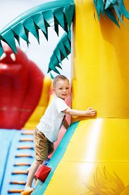 picture of inflatable slide  - Little cool boy have fun and play on an inflatable trampoline - JPG