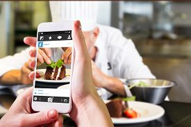 stock photo of pastry chef  - Hand holding smartphone against concentrated male pastry chef decorating dessert in kitchen - JPG