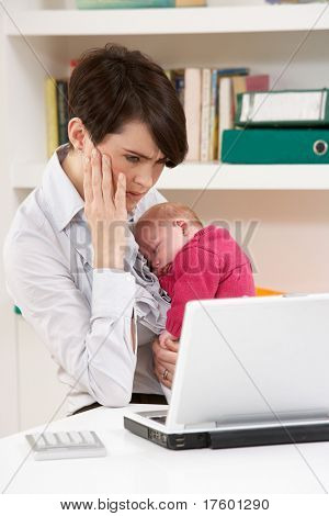 Stressed Woman With Newborn Baby Working From Home Using Laptop