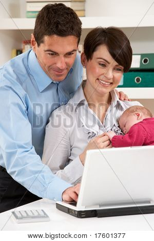 Parents With Newborn Baby Working From Home Using Laptop
