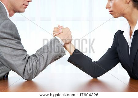 Portrait of business competitors doing arm wrestling and looking into each other?s eyes