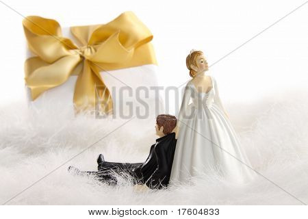 Wedding cake figurines with gold ribbon gift on white