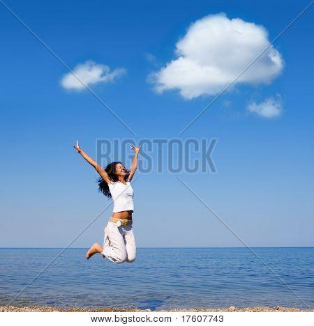 jovem feliz é saltar na praia