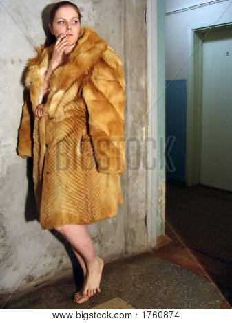 The Barefoot Girl In A Fur Coat Standing In A Corridor And Smoking