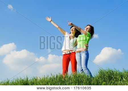 two young women on a green meadow and show something