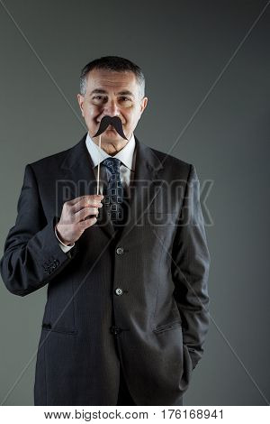 Smiling Businessman Holding A Mustache