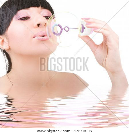 Young woman blowing soap bubble