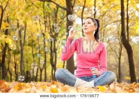 Young woman blowing soap bubble in the autumn park