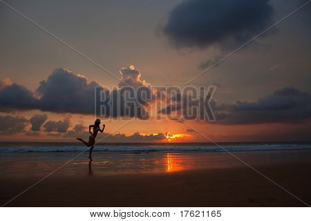 active woman running on a sunset in beach