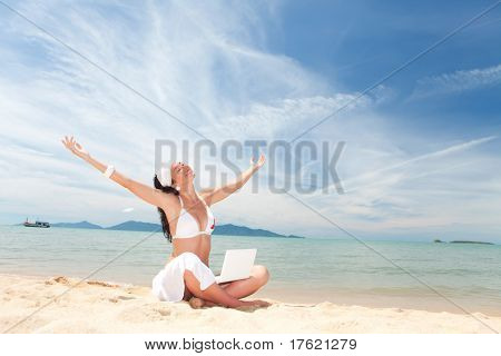 Cute woman with white laptop on the summer beach