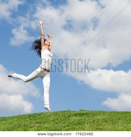 hübsche junge Frau, die auf grünen Rasen springen