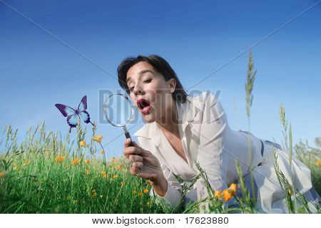 Astonished woman lying on a green meadow and observing a butterfly with a magnifying glass