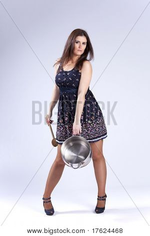 Fashion beautiful woman holding a kitchen pan and a wood spoon