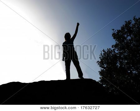 Backlit Of Person By Lifting The Arm As A Sign Of Victory