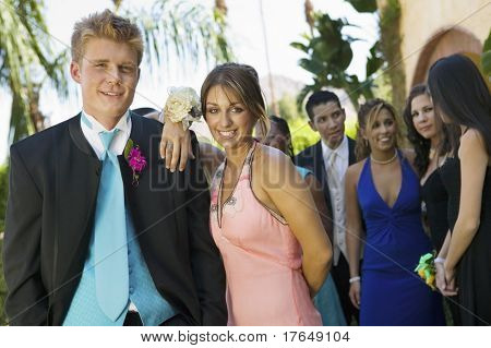 Well-dressed teenage couple standing outside school dance