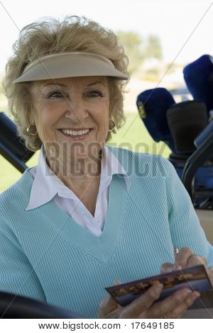 Senior woman holding golf score card, (portrait)
