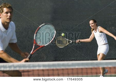 Mixed Doubles player hitting tennis ball, partner standing near net