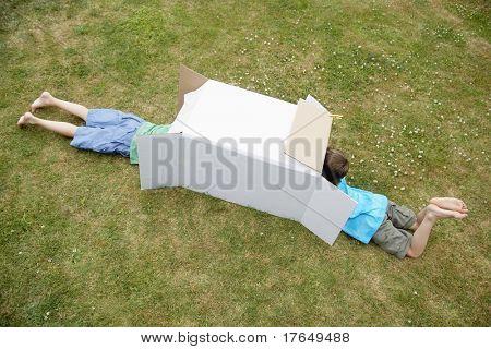 Two boys in backyard playing in cardboard box, high angle view