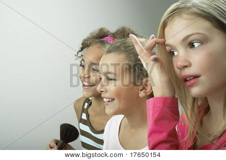 Girls standing side by side putting on make-up, fixing hair