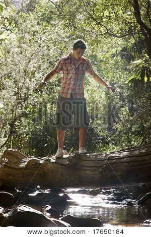 Teenage boy (16-17 years) walking tree trunk above stream