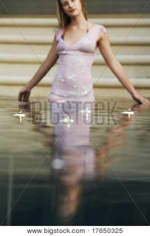 Young woman surrounded by floating candles standing in swimming pool, portrait