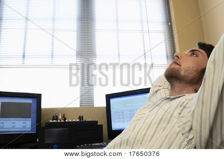 Man sitting by computers, relaxing, side view.
