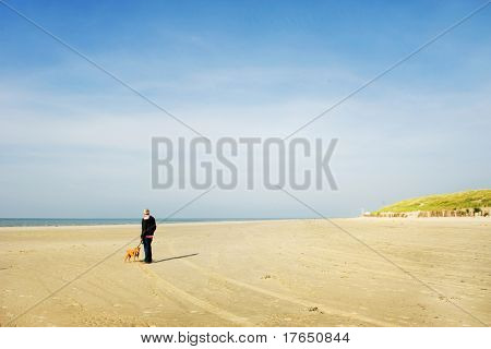 Walking the dog at the lonely beach