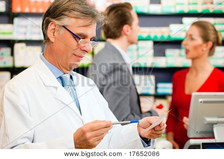 Pharmacist with customers in pharmacy, he is holding a prescription slip in his hands