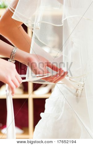 Bride at the clothes shop for wedding dresses; she is choosing a dress and the designer is assisting her