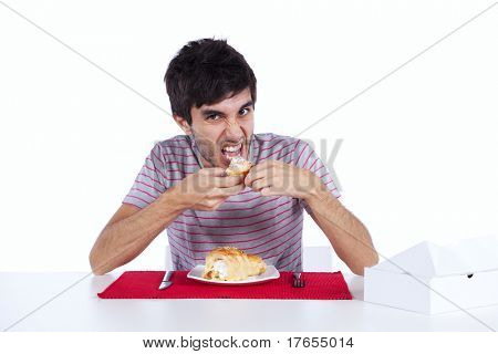 Young man eating a cake with lots of cream