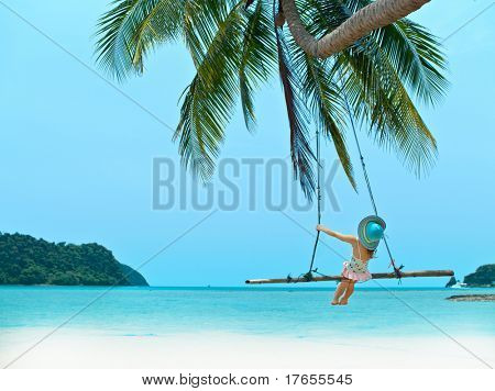 little girl on the beach on the swing