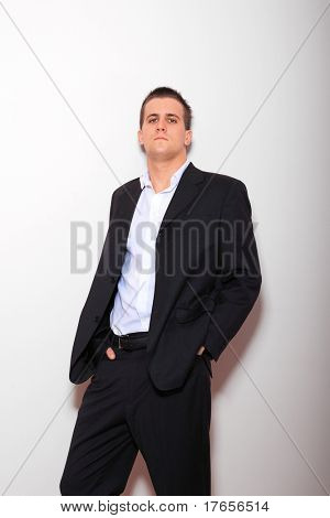 Full length of young business man standing against the wall with hands in pocket