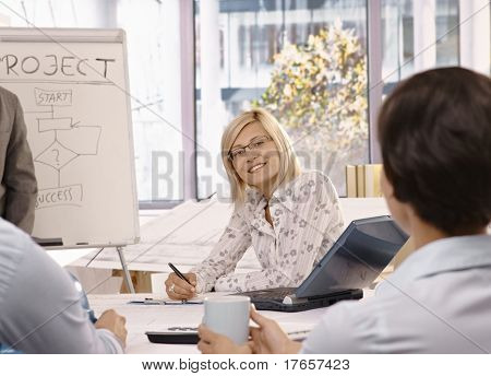 Smiling mid adult businesswoman sitting on team meeting, looking at camera.?
