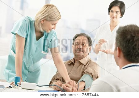 Nurse assisting doctor with measuring patient blood pressure in office.?