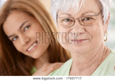 Closeup portrait of happy senior mother and young daughter, hugging, smiling.?