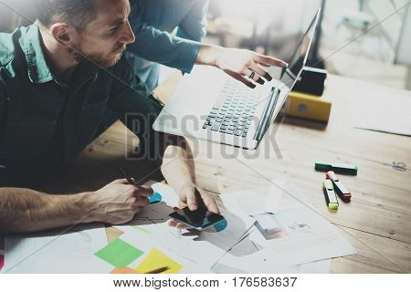 Closeup photo of two young coworkers working together in a sunny office.Man making notes on documents.Woman holding laptop on hands and showing to the partner.Horizontal, blurred