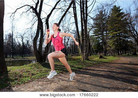 Panning shot of a female runner running outdoors