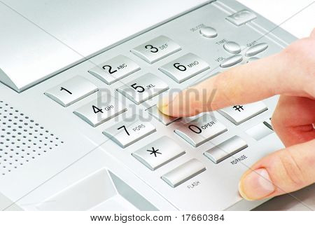 finger with  gray telephone keypad