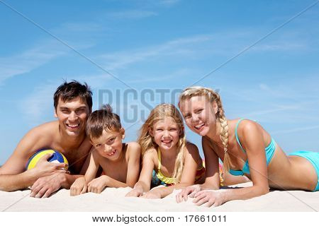 Photo of happy family lying on sand on background of blue sky