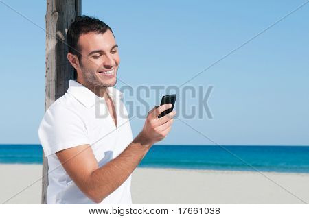 Happy young man looking at news and messaging on his smart phone at beach