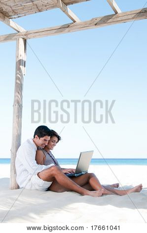 Beautiful young couple surfing the net together during summer vacation at tropical beach