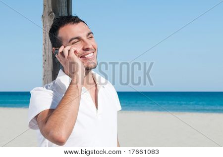 Happy smiling young man talking on mobile at summer beach