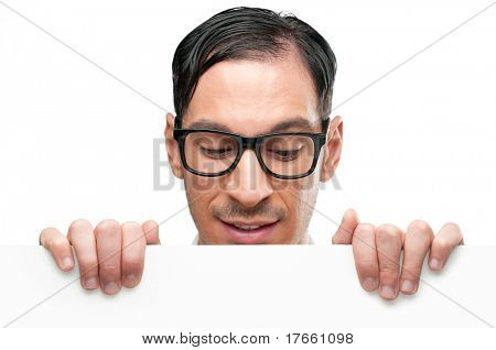 Happy nerd holding white placard for your text and looking down at it isolated on white background