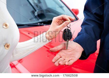 Man handing woman automobile keys. New Car