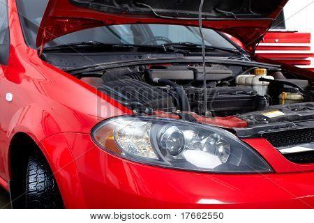 Coche con campana abierta en el taller de reparación de automóviles.