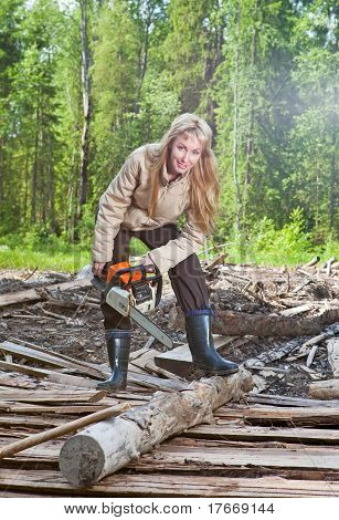 The young woman in wood saws a tree a chain saw