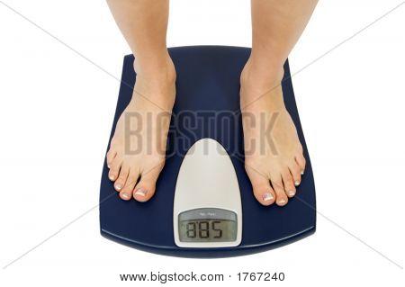 Female Feet Standing On A Bathroom Scale